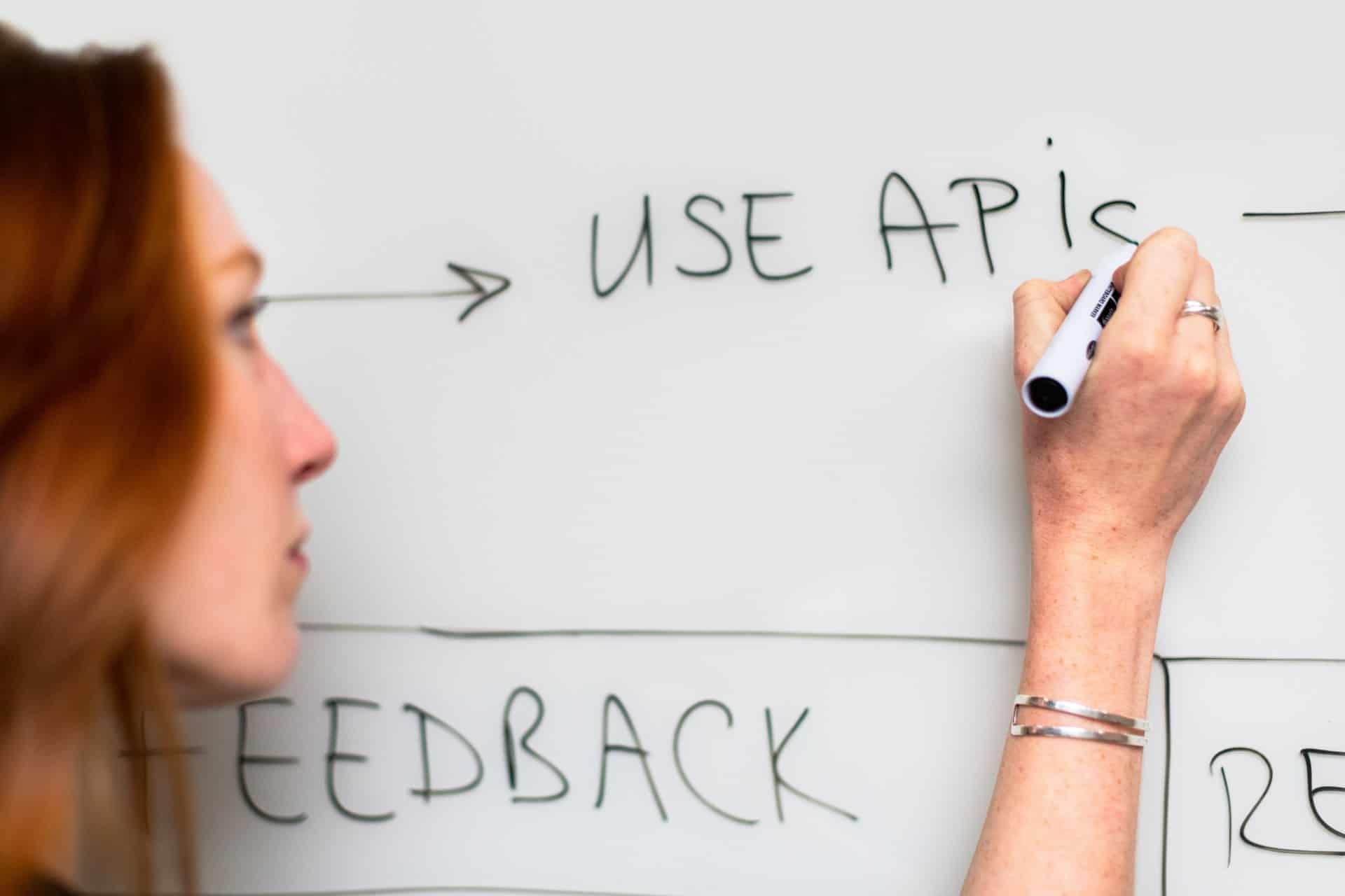 Woman writing API on whiteboard
