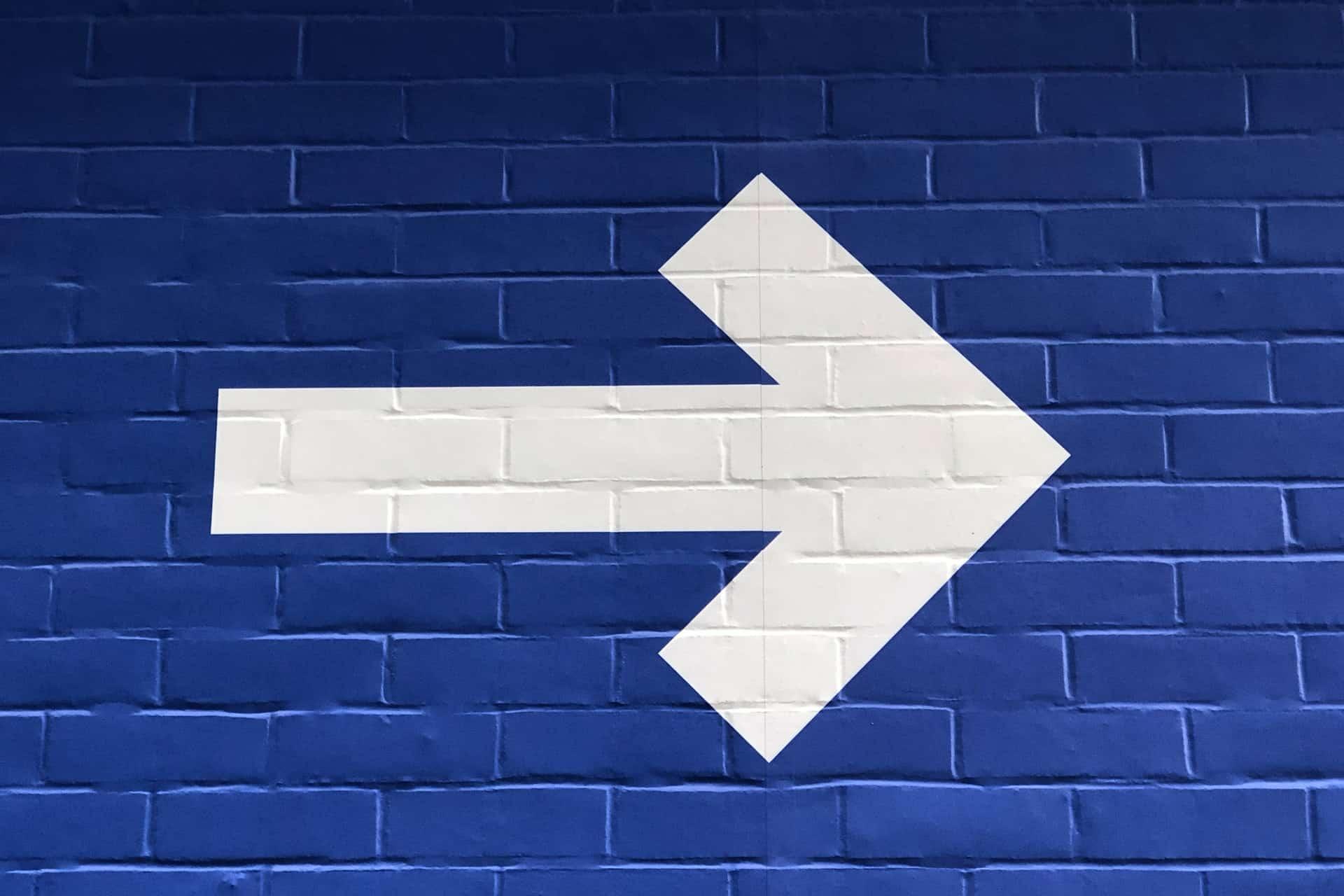 White arrow on blue wall
